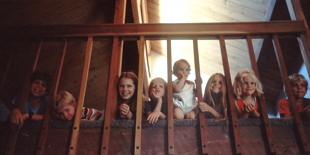 Children looking out of the stairwell railing inside a home.